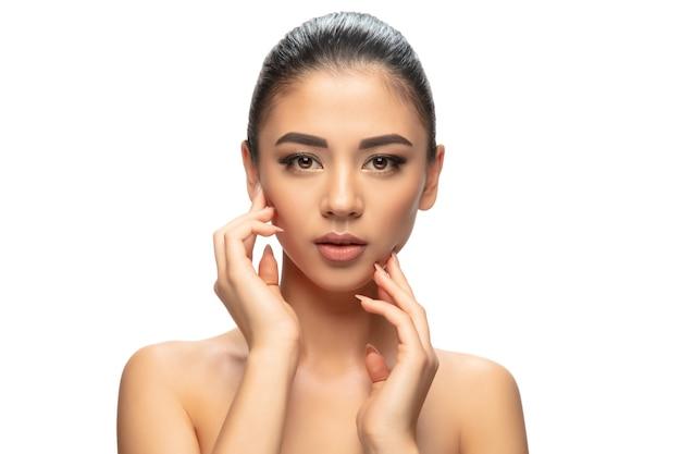 Dobrze utrzymany. portret pięknej młodej kobiety na tle białego studia. koncepcja kosmetyki, makijażu, zabiegów naturalnych i ekologicznych, pielęgnacji skóry. lśniący i zdrowy wygląd, moda, opieka zdrowotna. copyspace.