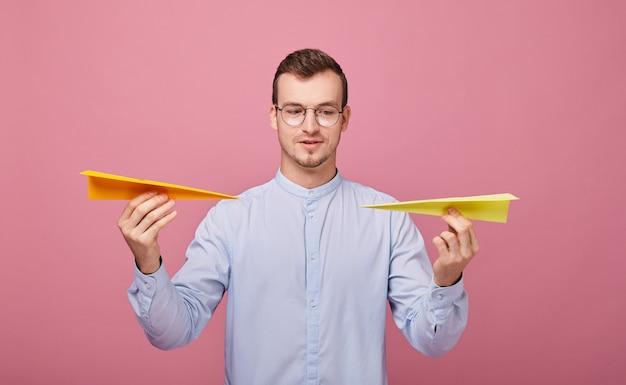 Dobrze wychowany młody mężczyzna w niebieskiej koszuli i okularach komputerowych stoi z dwoma papierowymi samolotami w dłoniach