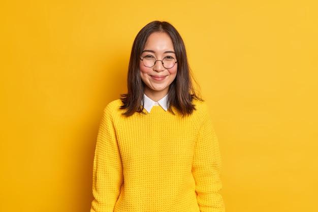 Dobrze wyglądająca azjatycka uczennica, która jest zadowolona z pochwał, uśmiecha się delikatnie z dołeczkami na policzkach i jest zachwycona