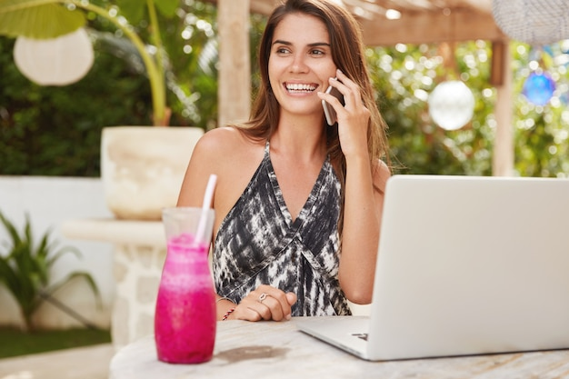 Dobrze wyglądająca brunetka rozmawia przez komórkę, siedzi przy laptopie podłączonym do darmowego internetu w kafeterii i patrzy radośnie na bok. piękna młoda kobieta lubi komunikację, drinki wstrząsnąć