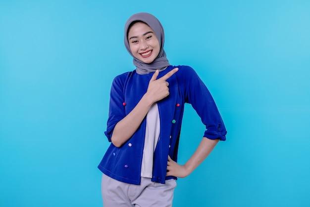 Dobrze wyglądająca charyzmatyczna młoda kobieta z hidżabem wskazującym prawą stronę na jasnoniebieskim tle