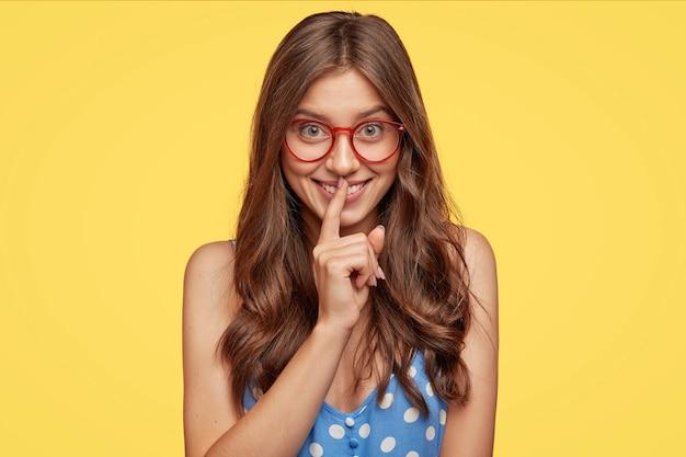 Dobrze wyglądająca dziewczyna rasy kaukaskiej pokazuje cisz lub ciszę, czule się uśmiecha, prosi, by nie ujawniać swojej tajemnicy