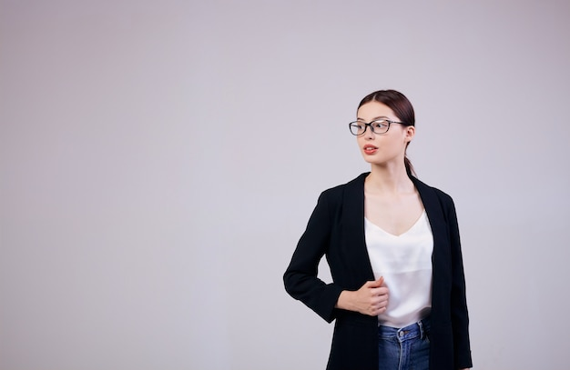 Dobrze wyglądająca kobieta biznesu stoi na szaro w czarnej kurtce, w białej koszulce i okularach komputerowych. zajęty.