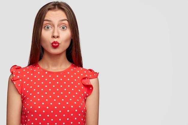 Dobrze wyglądająca kobieta z czerwoną szminką, pozowanie na białej ścianie