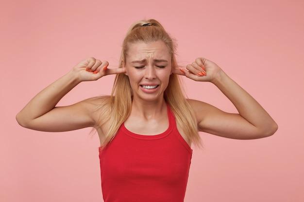 Dobrze wyglądająca młoda kobieta ze stojącą swobodną fryzurą, zakrywająca uszy rękami i marszcząca się, starająca się unikać głośnych dźwięków
