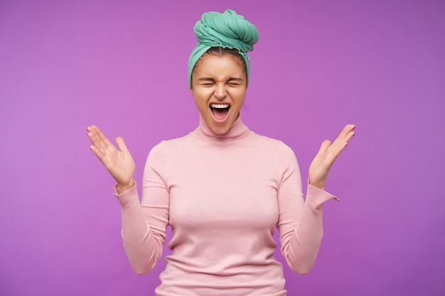 Dobrze wyglądająca młoda ładna brunetka kobieta ubrana w opaskę w węzeł, pozując nad fioletową ścianą, marszcząc brwi i krzycząc krzywo z zamkniętymi oczami