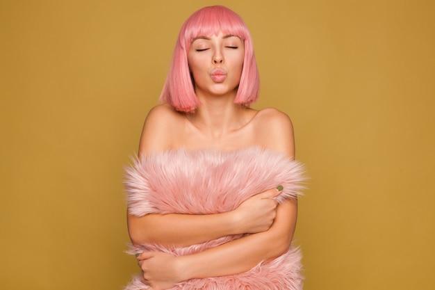 Dobrze wyglądająca młoda ładna dama z krótkimi różowymi włosami trzymająca puszystą poduszkę podczas pozowania na musztardowej ścianie, składająca usta w pocałunku w powietrzu z zamkniętymi oczami