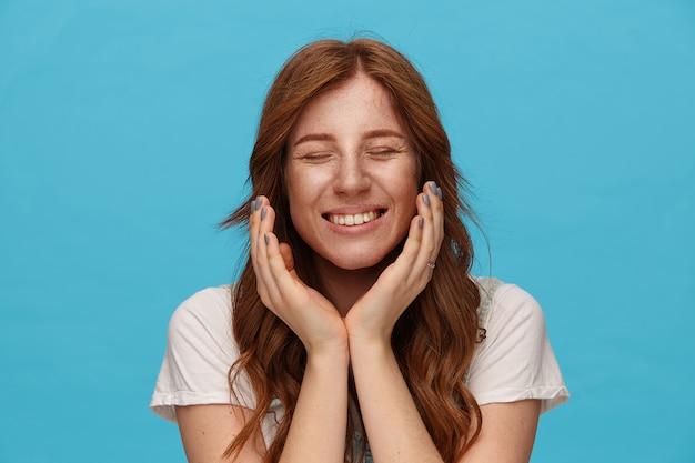 Dobrze wyglądająca młoda ładna ruda dama z naturalnym makijażem, trzymająca uniesione ręce pod twarzą i uśmiechnięta radośnie z zamkniętymi oczami, odizolowana na niebieskim tle