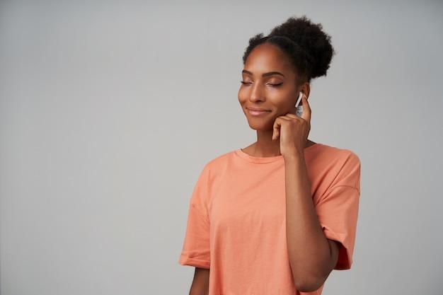 Dobrze wyglądająca młoda, pozytywna ciemnoskóra brunetka uśmiecha się radośnie z zamkniętymi oczami podczas słuchania muzyki przez słuchawki, odizolowane na szaro