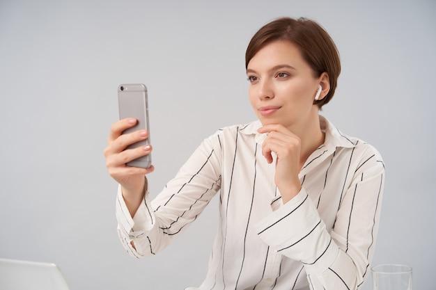 Dobrze wyglądająca młoda pozytywna krótkowłosa brunetka dama ubrana w eleganckie formalne stroje robiącą portret siebie ze smartfonem, trzymając brodę z podniesioną ręką siedząc na białym
