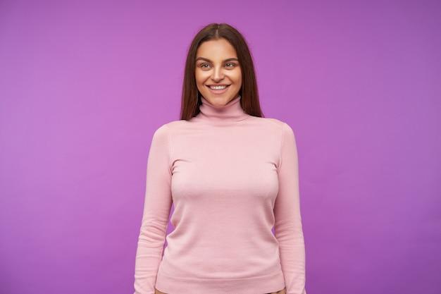 Dobrze wyglądająca młoda wesoła brunetka kobieta z luźnymi włosami, pokazująca swoje białe idealne zęby, uśmiechając się radośnie, odizolowana od fioletowej ściany z opuszczonymi rękami