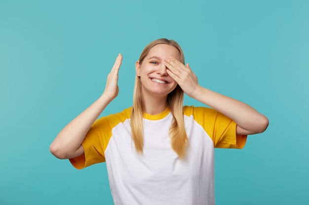 Dobrze wyglądająca młoda wesoła długowłosa blondynka trzyma podniesioną rękę na oku i uśmiecha się szeroko do kamery, stojąc na niebieskim tle w swobodnej koszulce