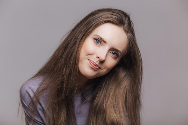 Dobrze wyglądająca niebieskooka modelka z ciemnymi długimi włosami i niebieskimi atrakcyjnymi oczami, pozuje na szarym tle