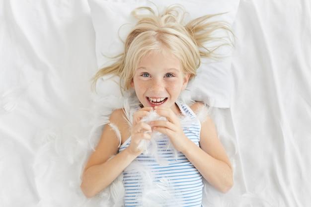 Dobrze wyglądająca piegowata dziewczyna bawi się z bratem w łóżku, walczy z poduszkami, łapie pióra, ma radosny wyraz twarzy. blondynka piegowata dziewczyna bawi się piórami leżąc na białej poduszce na łóżku