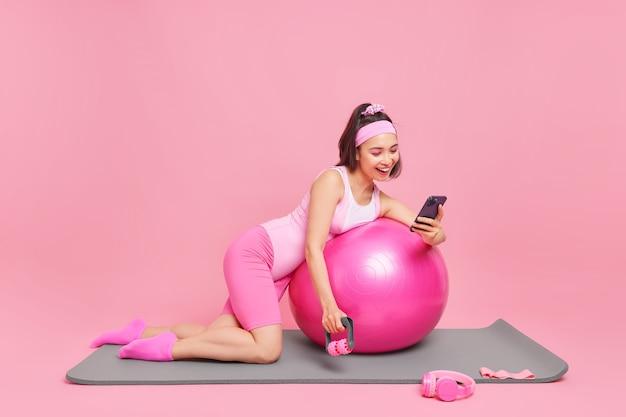 Dobrze wyglądająca, pozytywna, sportowa azjatycka modelka fitness pozuje ze sprzętem sportowym na macie, ubrana w odzież sportową, sprawdza kalorie w specjalnej aplikacji, ma trening treningowy