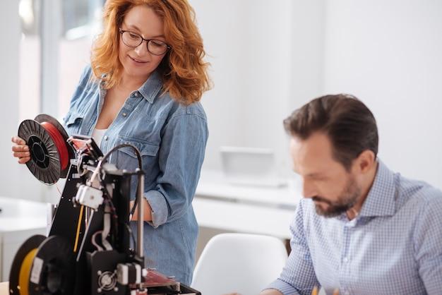 Dobrze wyglądająca, sympatyczna, miła kobieta stojąca w pobliżu drukarki 3d i zmieniająca filament podczas modelowania 3d