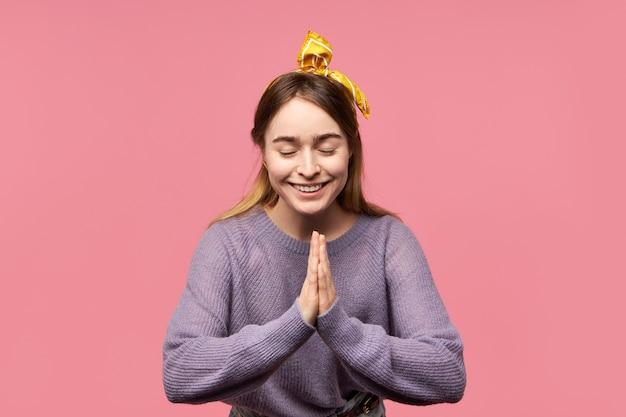 Dobrze wyglądająca urocza młoda kobieta z jedwabnym szalikiem na głowie, z zamkniętymi oczami i uśmiechnięta
