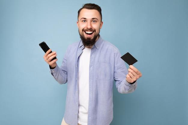 Dobrze wyglądający atrakcyjny uśmiechnięty brunet zarośnięty młody człowiek ubrany w dorywczo niebieską koszulę i