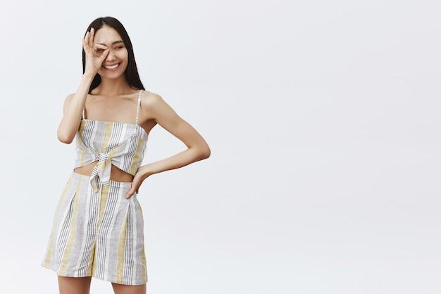Dobrze wyglądający, beztroski, modny model z mediów społecznościowych w dopasowanym stroju, pokazujący dobry lub dobry gest nad okiem, trzymający rękę na talii i spoglądający w bok z szerokim radosnym uśmiechem na szarą ścianę