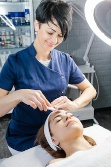 Dobrze wyglądający lekarz-kosmetolog czyni z aparatu zabieg ultradźwiękowego oczyszczania skóry twarzy