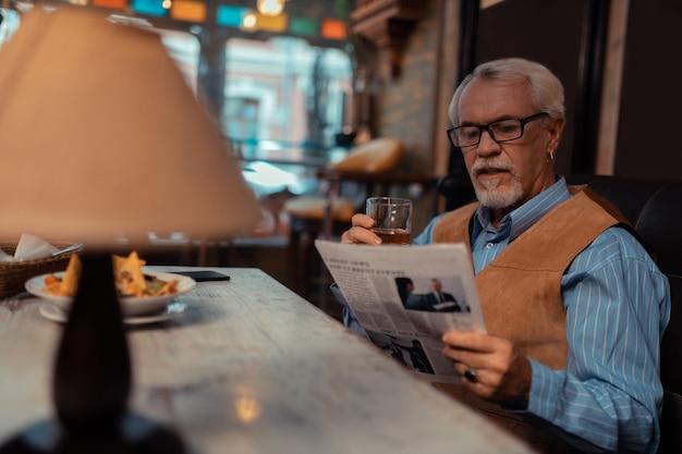 Dobrze wyglądający mężczyzna. przystojny emeryt, czytający gazetę i pijący whisky w pubie