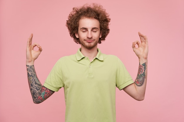 Dobrze wyglądający, młody, kręcony, brązowowłosy wytatuowany mężczyzna z zamkniętymi oczami podczas medytacji i składania palców w geście mudry, odizolowany na różowym tle