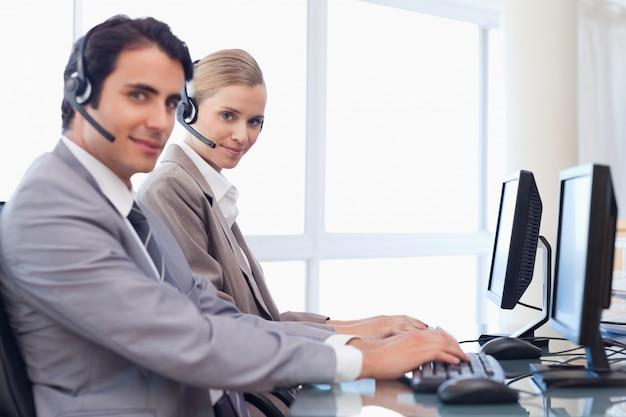 Dobrze wyglądający operatorzy korzystający z komputera