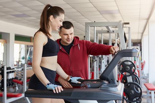 Dobrze wykwalifikowany trener wyjaśnia swojemu klientowi, jak korzystać z bieżni, w czarnej koszulce i czerwonej sportowej kurtce. piękna brunetka dama przestrzega wszystkich instrukcji, jest skoncentrowana i uważna.