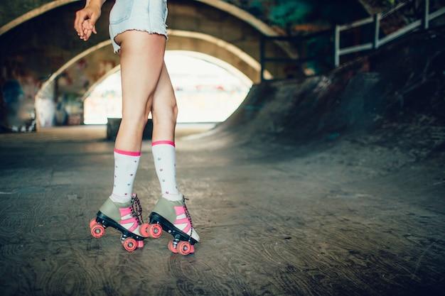 Dobrze zbudowane i szczupłe nogi kobiety z szarymi skarpetami i rolkami