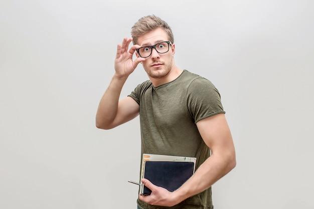 Dobrze zbudowany i silny młody mężczyzna pozowanie na kamery. patrzy prosto i trzyma rękę na okularach. facet ma książki w drugiej ręce. pojedynczo na białym tle.