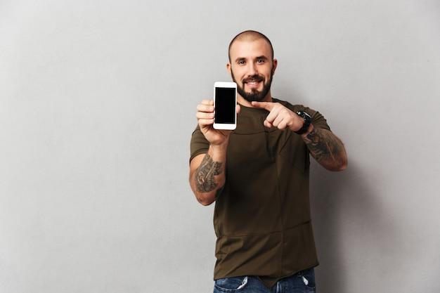Dobrze zbudowany szczęśliwy człowiek 30s trzyma telefon komórkowy i wskazując palcem na czarny ekran, odizolowane na szarej ścianie