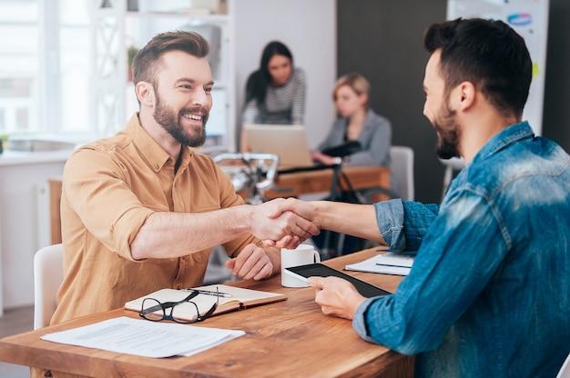 Dobrze zrobiony! dwóch pewnych siebie młodych mężczyzn ściskających dłonie i uśmiechających się siedząc przy biurku w biurze z dwiema osobami pracującymi w tle