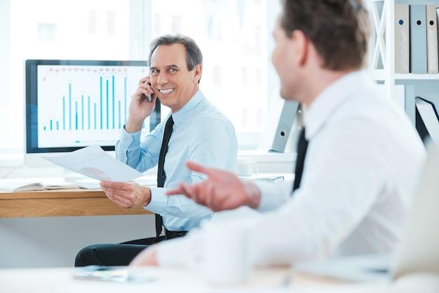 Dobrze zrobiony! dwóch wesołych ludzi biznesu w formalnej odzieży, rozmawiających o czymś i uśmiechających się