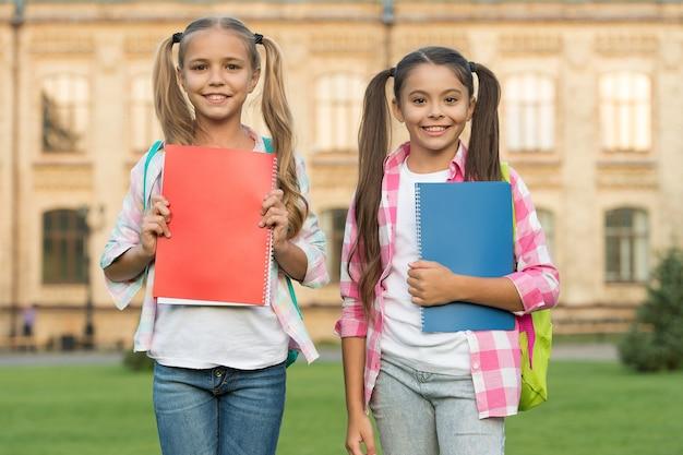 Dobrzy przyjaciele, dobre książki. szczęśliwe dzieci trzymają książki. urocze moli książkowe na zewnątrz. biblioteka szkolna. studia literaturowe i językowe. gramatyka angielska. edukacja i wiedza. trzymanie głowy w książkach przez cały dzień.