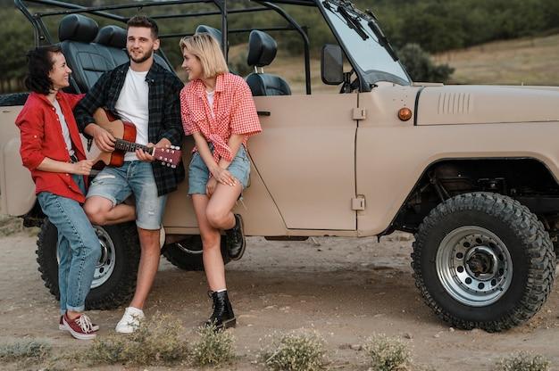 Dobrzy przyjaciele grający na gitarze podczas podróży samochodem