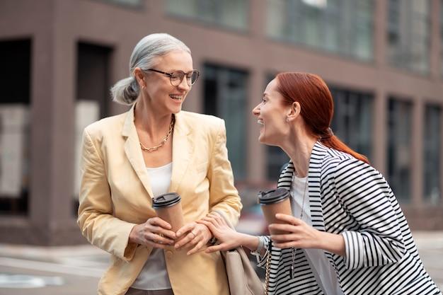Dobrzy przyjaciele. młoda bizneswoman śmieje się, patrząc na swojego zadowolonego starszego przyjaciela stojącego obok niej na zewnątrz