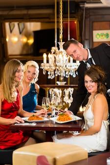 Dobrzy przyjaciele na lunch w eleganckiej restauracji, kelner podał kolację