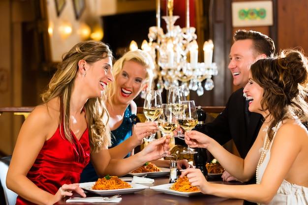 Dobrzy przyjaciele na obiad lub lunch w eleganckiej restauracji, szczęk szklanek