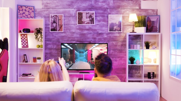 Dobrzy przyjaciele siedzą na kanapie i grają w sieciowe strzelanki za pomocą bezprzewodowych kontrolerów.