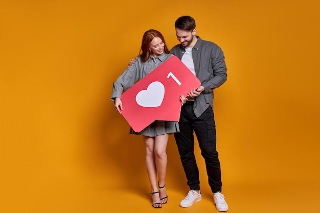 Doceń zawartość za pomocą przycisku w kształcie serca. para trzyma jak ikona mediów społecznościowych na pomarańczowej ścianie