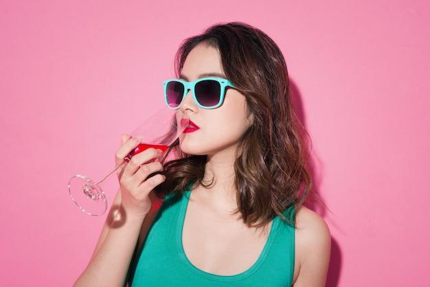 Docenianie azjatyckiej dziewczyny z profesjonalnym makijażem i stylową fryzurą trzymającą kieliszek szampana.