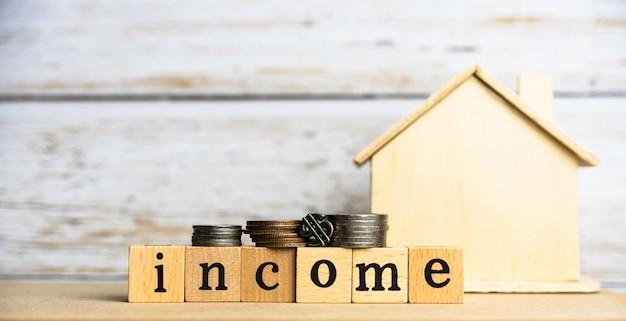 Dochód słowo napisane na drewnianym bloku i monetach obok niewyraźnego małego domu, na drewnianej desce