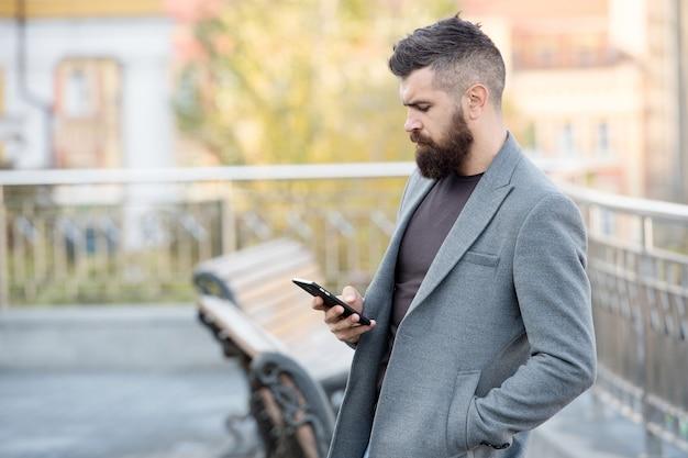 Docieraj do ludzi w podróży dzięki sms-marketingowi. brodaty mężczyzna czytał sms miejskie na zewnątrz. smsowanie. urządzenie przenośne. nowa technologia. nowoczesne życie. komunikacja biznesowa.