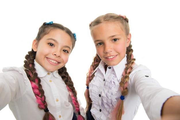 Dodaj magii swoim zdjęciom dzięki filtrowi upiększającemu. piękno wygląd małych dzieci na białym tle. małe dzieci z uroczymi uśmiechami na twarzach urody. szczęśliwe dziewczyny piękności z długimi włosami, uśmiechając się do kamery.