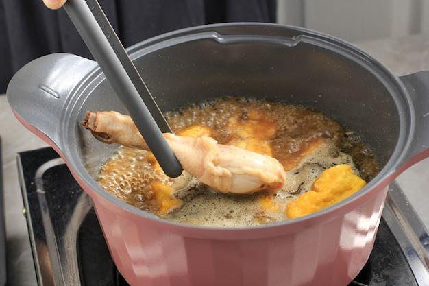 Dodaj udko z kurczaka do gotowanej przyprawy, proces gotowania, dzięki któremu opor ayam, indonezyjskie curry z kurczaka popularne w lebaran