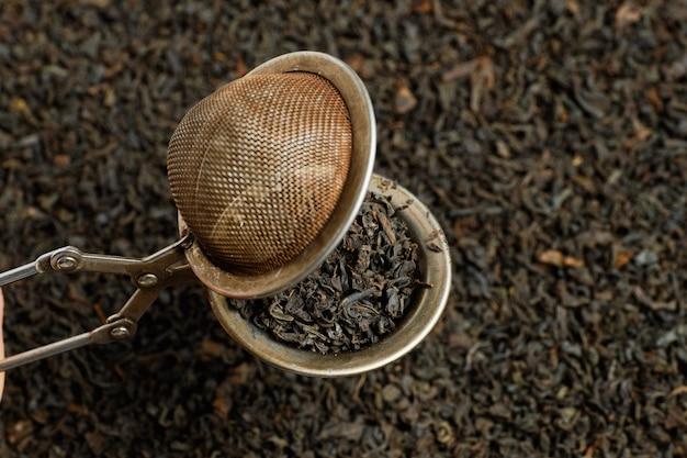 Dodatek do parzenia jest otwarty na tle czarnej herbaty.