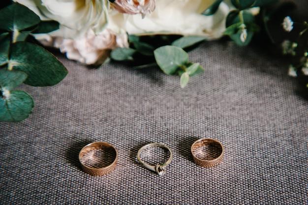 Dodatki ślubne: kwiaty, dziurka na guziki, złote obrączki ślubne na rustykalnym worku, retro brązowe tło. koncepcja wakacji. stylowy bukiet kwiatów panny młodej. ścieśniać.