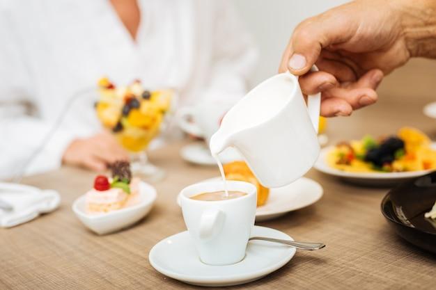 Dodawanie kremów. mężczyzna mieszający ciężkie kremy do gorącego espresso, jedzący przyjemne śniadanie