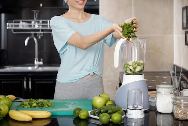 Dodawanie składników do blendera w kuchni