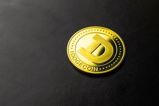Dogecoin kryptowaluta na czarnym tle zbliżenie, jedna złota moneta, zdjęcie koncepcji biznesu i finansów